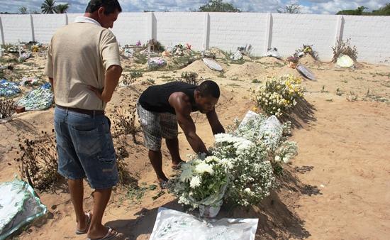 Coveiro arruma a sepultura de Janiele com as flores depositas pelos familiares e amigos.