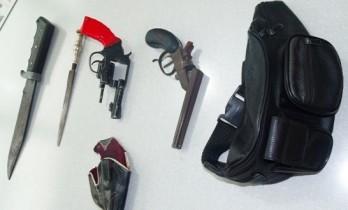 Pochete da vítima e o revolver usado no duplo homicídio (detalhe em vermelho)