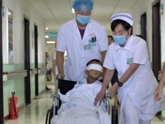 Guo Bin é conduzido em cadeira de rodas por equipe médica de hospital em Taiyuan