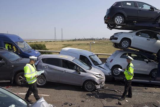 Policiais examinam os destroços dos carros esmagados na ponte Sheppey