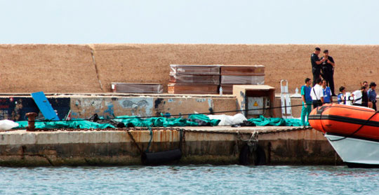 Policiais e voluntários de resgate italiano observam os corpos cobertos dos imigrantes no porto de Lampedusa