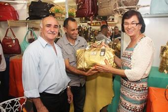 Neusa ao lado do prefeito municipal exibe uma bolsa de grande qualidade produzida em Ipirá.