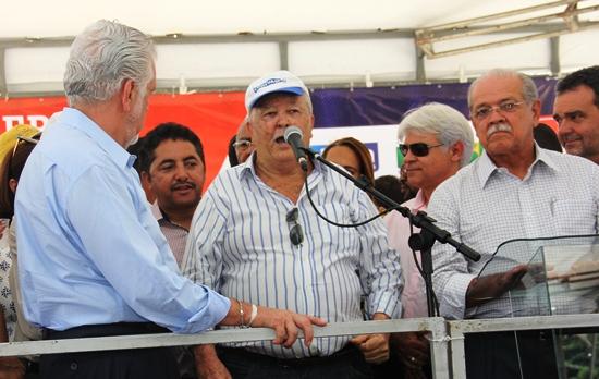 Nelsinho de cabelos alvos e óculos escuros e no direito do prefeito Roberto Carlos