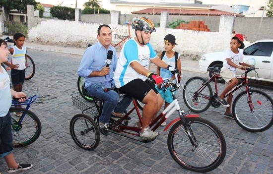 "Jorge Araújo desfila pela rua na ""garupa"" da inusitada bike de Boba."