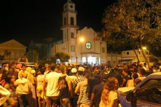 Populares lotam a praça e ao fundo a Catedral no momento da missa.
