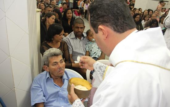 Momento que o padre serve a eucaristia a seu pai.