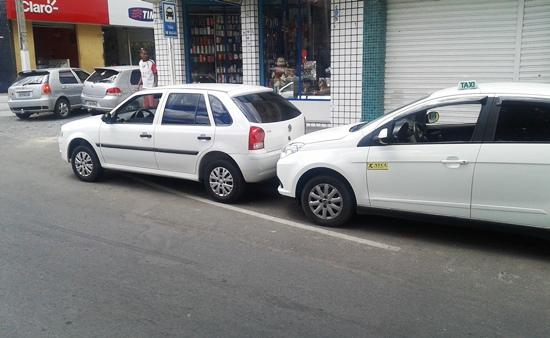 Esse Gol da frente está numa esquina e debaixo de uma placa informado 8 vagas para taxi.
