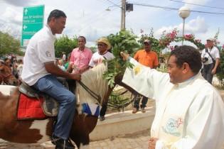 O vigário molhando o ramo dentro de um balde deu a benção a cada vaqueiro.
