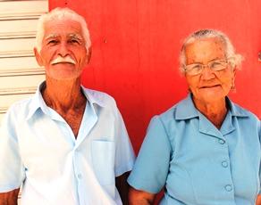 """Dona Lili cumpre seu ritual religioso ao lado do deu esposo conhecido por """"Pequeno"""" que também tem 80 anos."""