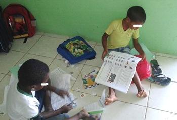 Crianças assistem aula sentados no chão.