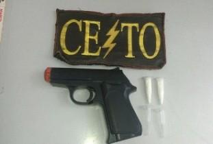 Arma de brinquedo apreendida com uma substância que pode ser cocaína.