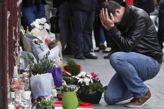 Homem se emociona diante de objetos de tributo deixados em frente à cafeteria Carillon, em Paris, onde um dos ataques terroristas ocorreu