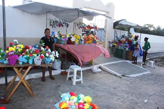 Em frente ao cemitério velho ramalhetes de flores artificias sendo vendido pelo valor de R$ 2 a R$ 20.