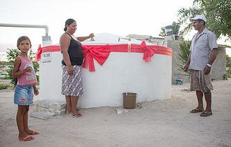Dona de casa comemora recebimento de uma cisterna.