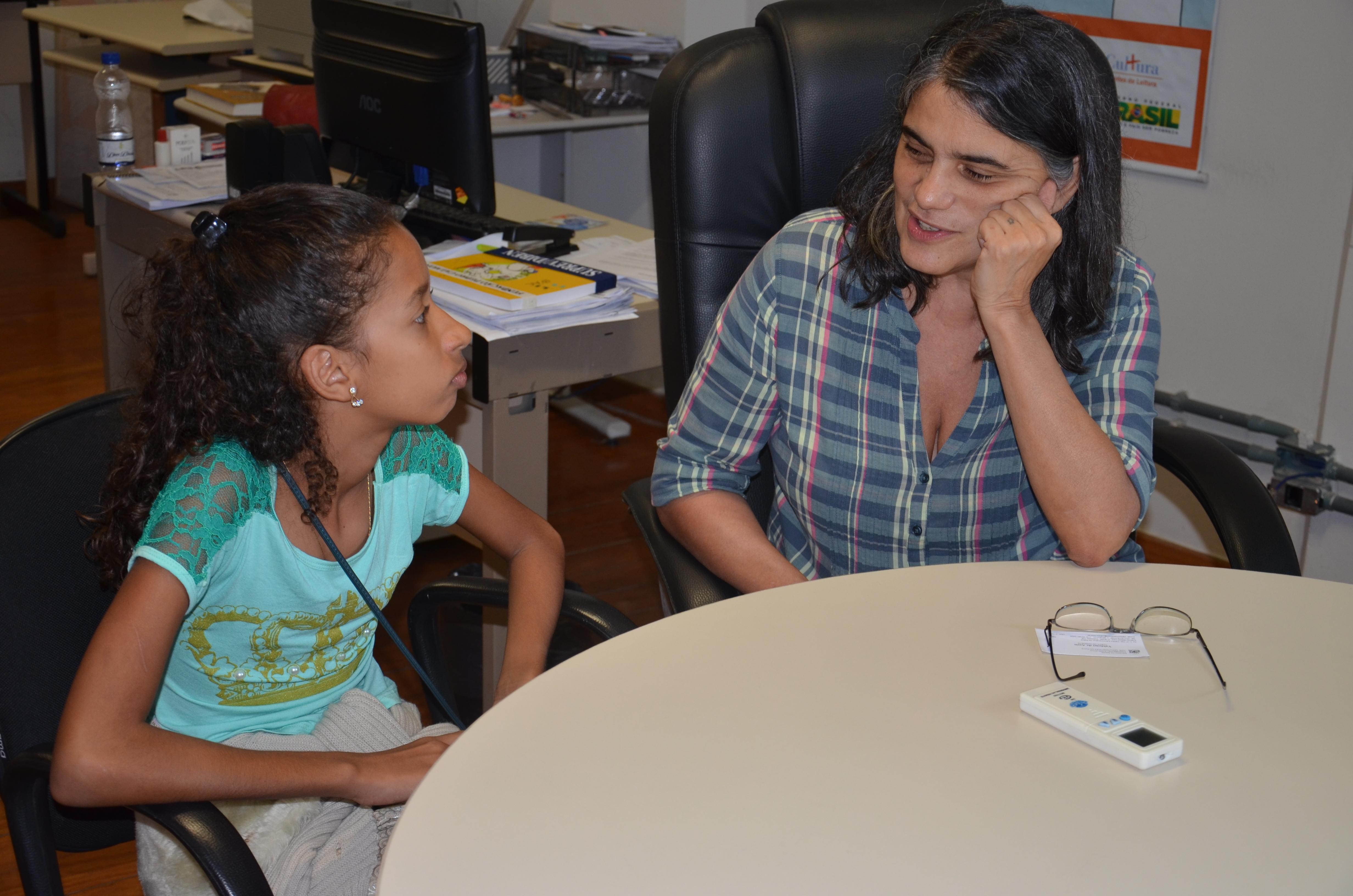 Mariangela, da Fundação Pedro Calmon, se impressiona com a garota Clarinha.