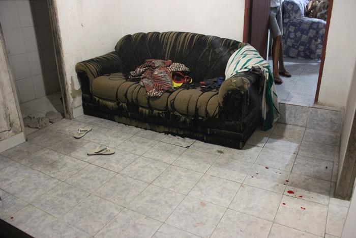 Vítima estava deitada neste sofa. Marcas de sangue e cápsulas de projétil calibre 380 servirão para o trabalho dos peritos tentar elucidar o crime
