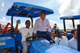 Gika Lopes ao lado de um líder comunitário que exibe a chave do trator