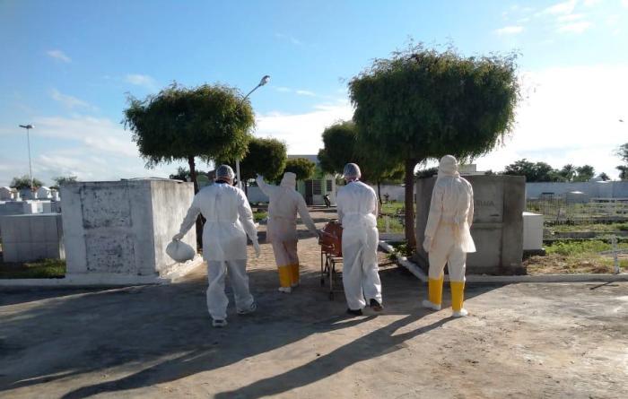 Funcionários de uma Funerária fazem uso de roupa especial para evitarem contaminação
